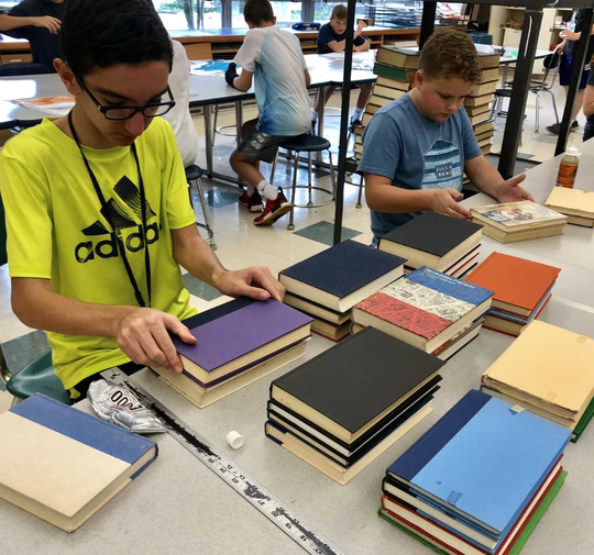 Students assemble stacks of books for mural at Eisenhower Middle School in Wyckoff.