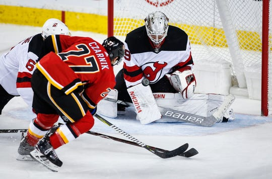 New Jersey Devils goalie Mackenzie Blackwood, right, blocks the net on Calgary Flames' Austin Czarnik during the second period of an NHL hockey game Tuesday, March 12, 2019, in Calgary, Alberta.