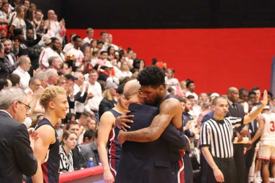 Mike Holloway Jr. hugs coach Greg Herenda as Fairleigh Dickinson is about to win the Northeast Conference men's basketball title at top-seeded St. Francis (Pa.) on Tuesday, March 13, 2019