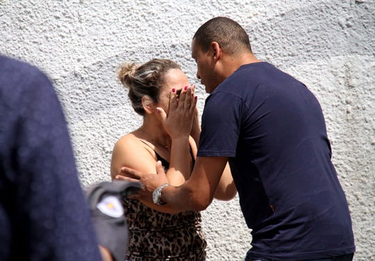 A man comforts a woman at the Raul Brasil State School in Suzano, Brazil, Wednesday, March 13, 2019. The state government of Sao Paulo said two teenagers, armed with guns and wearing hoods, entered the school and began shooting at students. They then killed themselves, according to the statement.