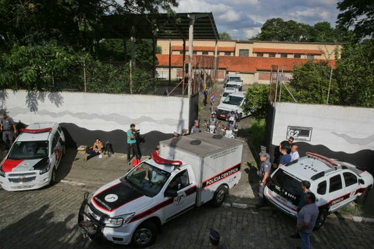 Forensic vehicles transport the bodies of the people who were killed in a school shooting at the Raul Brasil State School in Suzano, in the greater Sao Paulo area, Brazil, Wednesday, March 13, 2019. Two masked former students armed with guns, knives, axes and crossbows descended on the school.