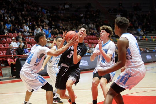Oñate's Jordy Moreno attacks the basket and gets fouled against Cleveland during Wednesday's 5A state quarterfinals at Dreamstyle Arena in Albuquerque.
