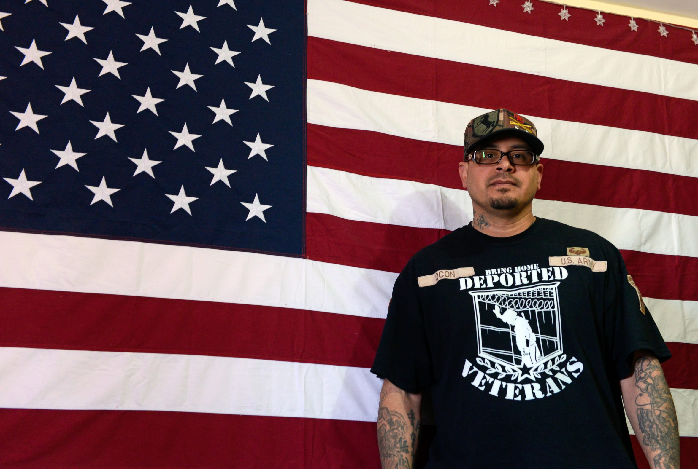 Ivan Ocon, who grew up in Las Cruces but was deported to Mexico for breaking the law, stands in front of a U.S. flag at his home in Juárez.