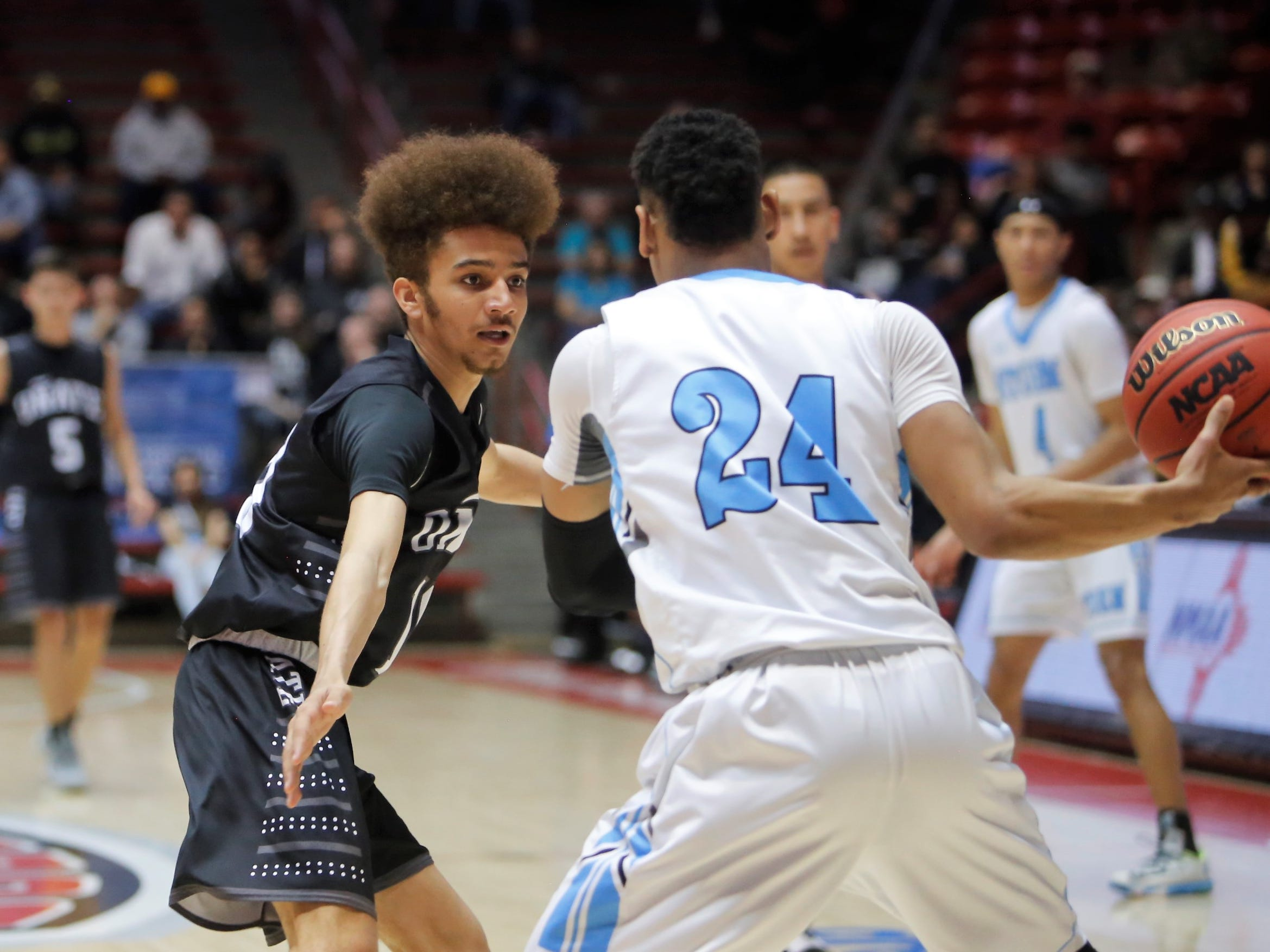 Oñate's Derek Silva looks to get a defensive stop against Cleveland's Aamer Muhammad during Wednesday's 5A state quarterfinals at Dreamstyle Arena in Albuquerque.