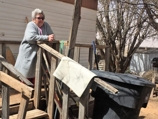 Luisa Lucero Lira stands on her front porch after her roof flew off during a powerful windstorm on Wednesday, March 13, 2019.