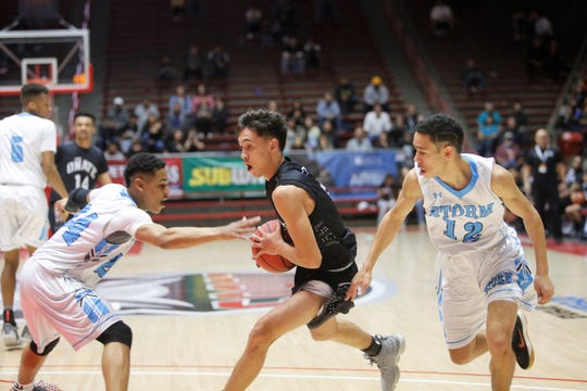 Oñate's Ricky Lujan drives in for a layup against Cleveland's Aamer Muhammad (24) and Nakqi Smith (12) during Wednesday's 5A state quarterfinals at Dreamstyle Arena in Albuquerque.