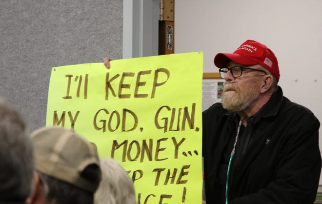 A man holds a sign opposing gun control bills like House Bill 83 Tuesday during an Aztec City Commission meeting.