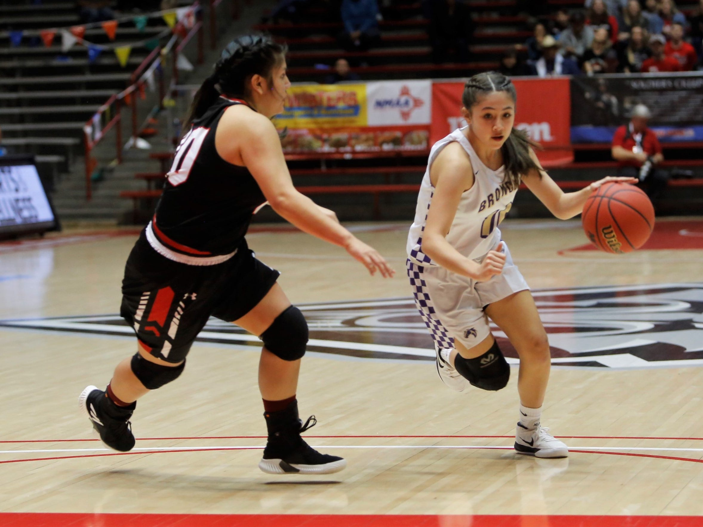 Kirtland Central's Monique Shim drives toward the basket against Portales' Codi Flores during Tuesday's 4A state quarterfinals game at Dreamstyle Arena in Albuquerque.