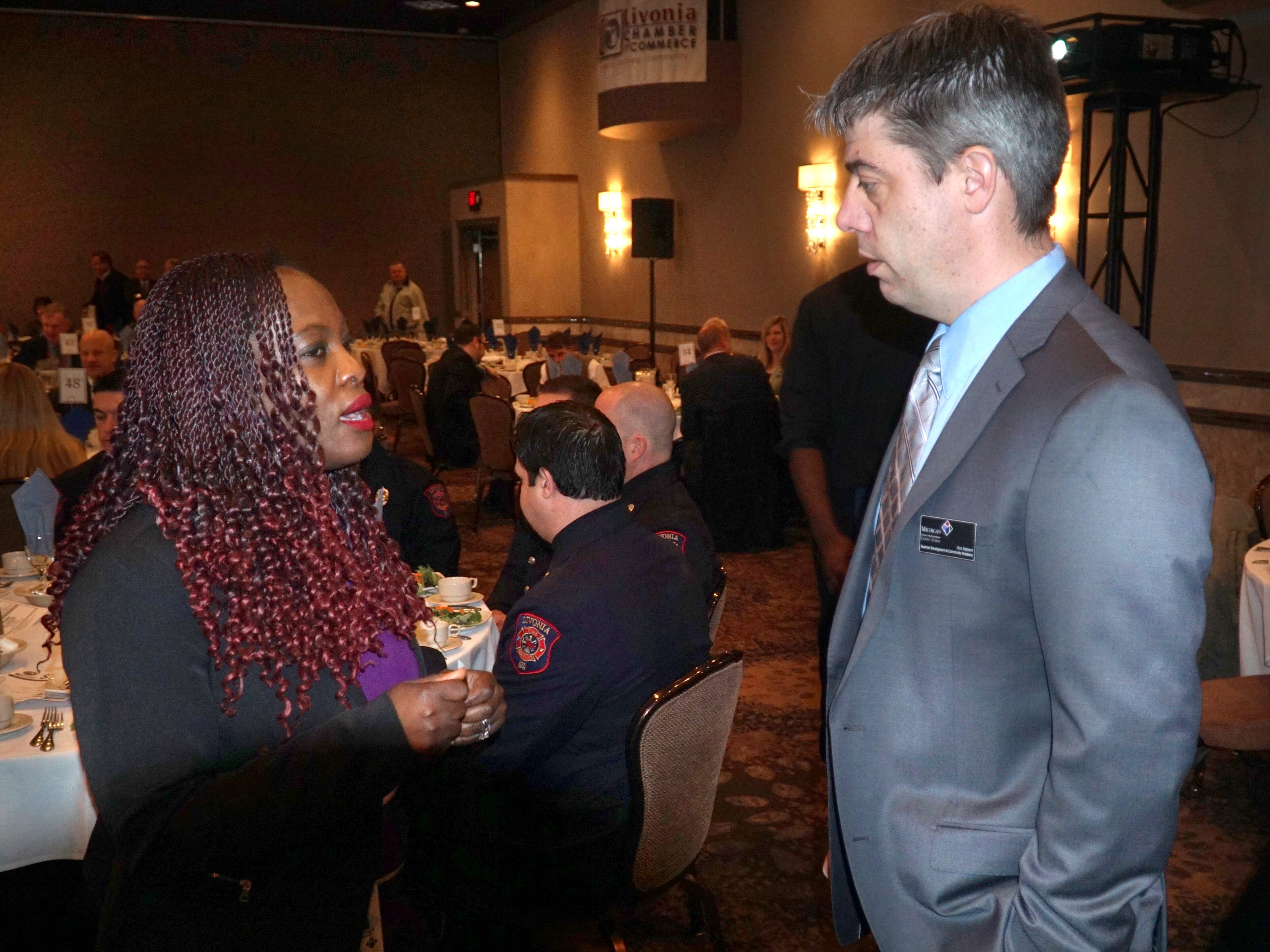 Marjorie Riezkhoff and Eric Rothert, both colleagues at the Michigan Schools and Government Credit Union talk before the begining of the State of the City address for Livonia at the Laurel Manor on March 13.