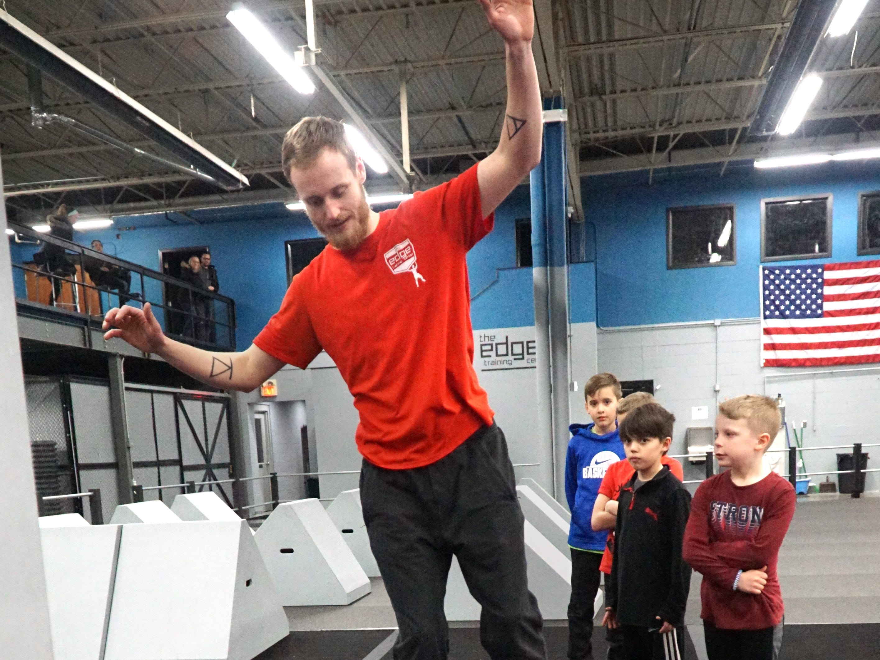 Sam Sherbrooke, son of Carey, demonstrates to a group of kids how he'd like them to walk across a balance pipe section of an obstacle course on March 12.