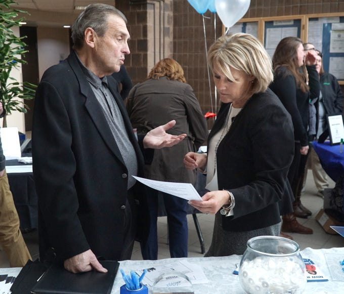 """Jan Woznick hands his resume and talks with Express Employment Solutions' Lynn Coburn, right, during the March 13 City of Novi Job Fair at the Civic Center. There were more than 40 local business at the fair offering both full and part-time and seasonal work. Woznick said that he was """"Looking for something to do the rest of my life"""", and talking with lots of employers."""