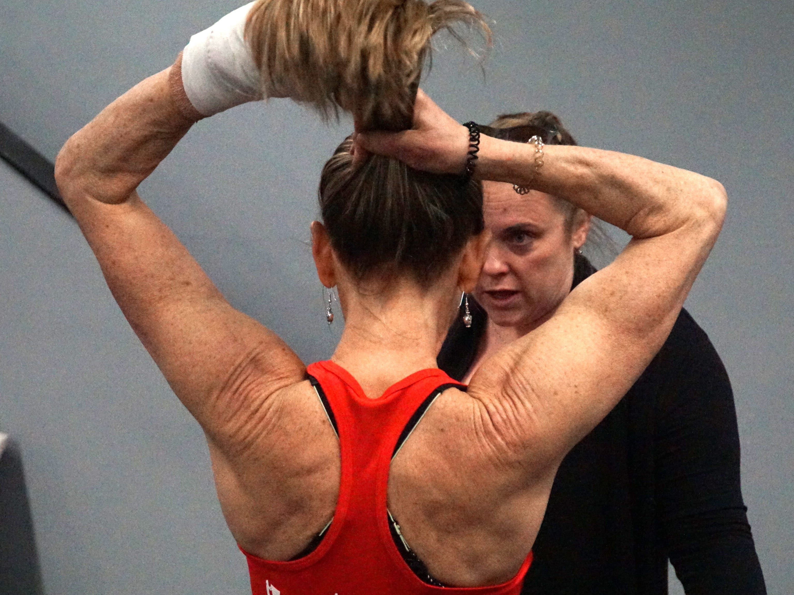 The Edge Training Center owner Carey Sherbrooke speaks to a visitor to her gym as ties her hair up in a ponytail before leading a group of youngsters through some obstacle course work on March 13. Sherbrooke's left wrist is in a bandage as she'd had carpal tunnel surgery just a few days before.