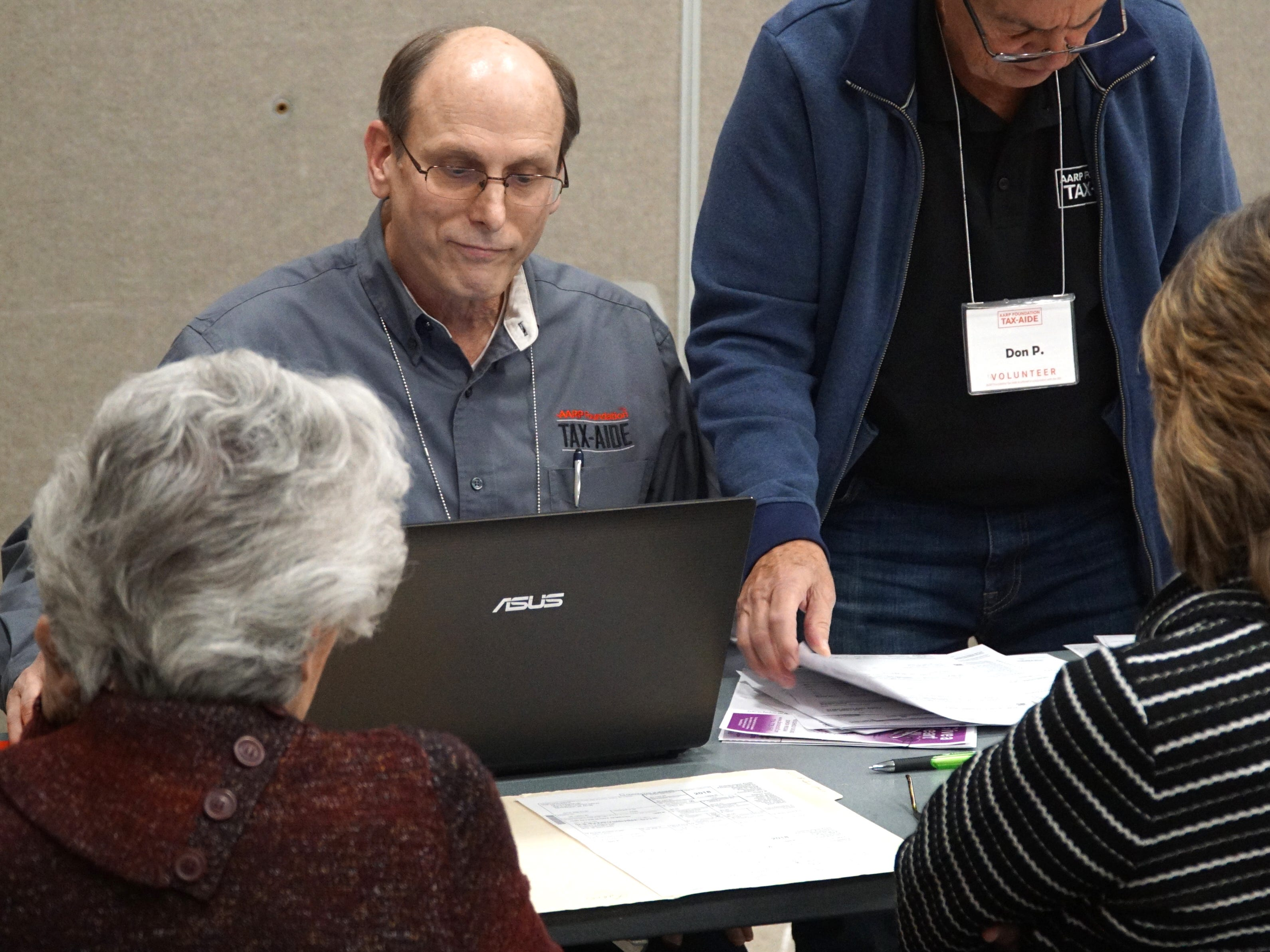 Tax Aide Jack Motz, left, helps to check the tax-filings of some visitors to AARP's free 2018 tax filing gathering on March 13 at the Novi Civic Center.
