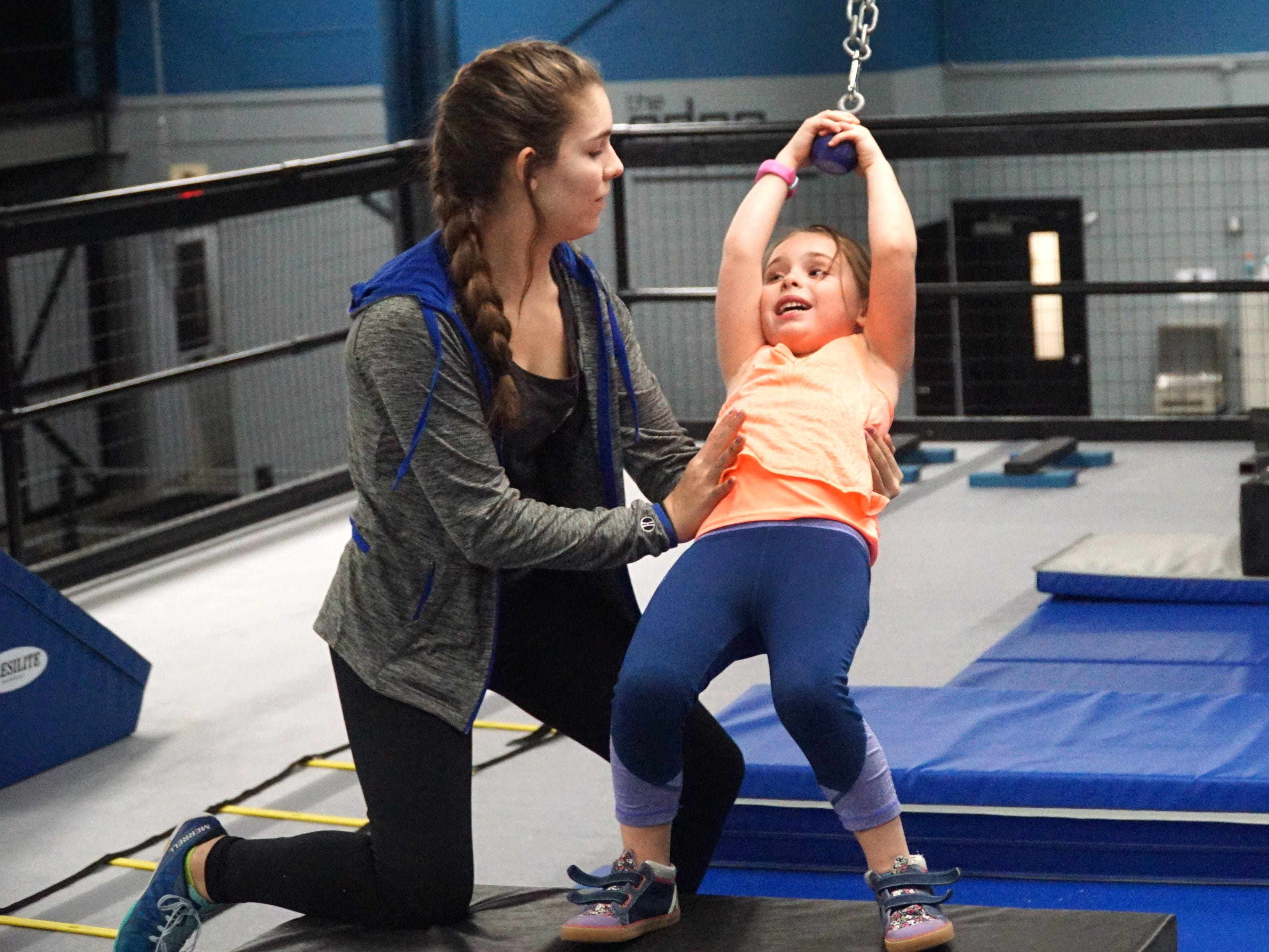 Maggie Lambert, left, assists Morgan Hudya as the youngster swings across a small gap at the Edge Training Center's upper level course.