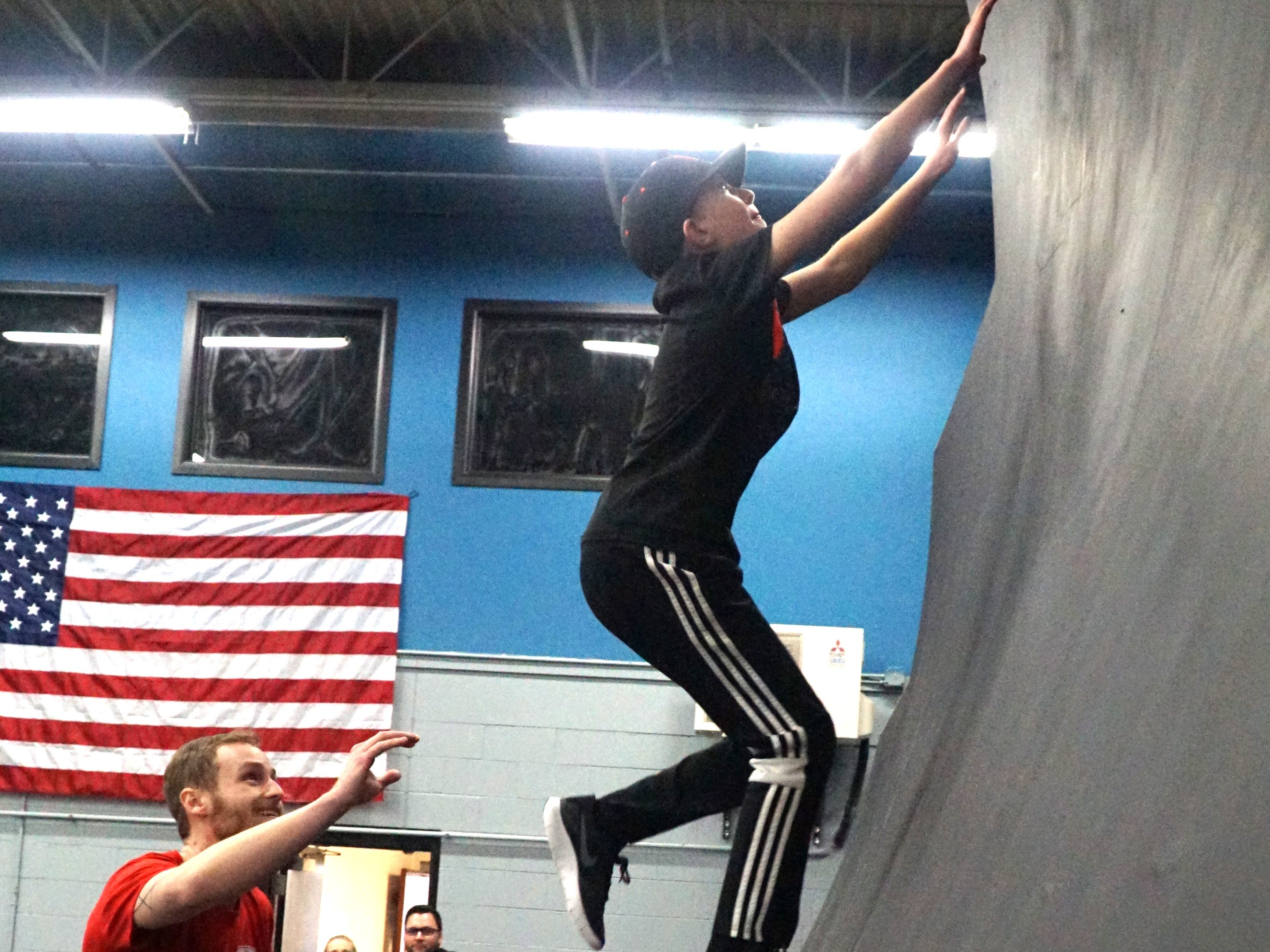 Sam Sherbrooke, left, an employee of The Edge Training Center in Plymouth - spots the progress of student Aidan Stover, 11, as he runs up the gym's curved wall.