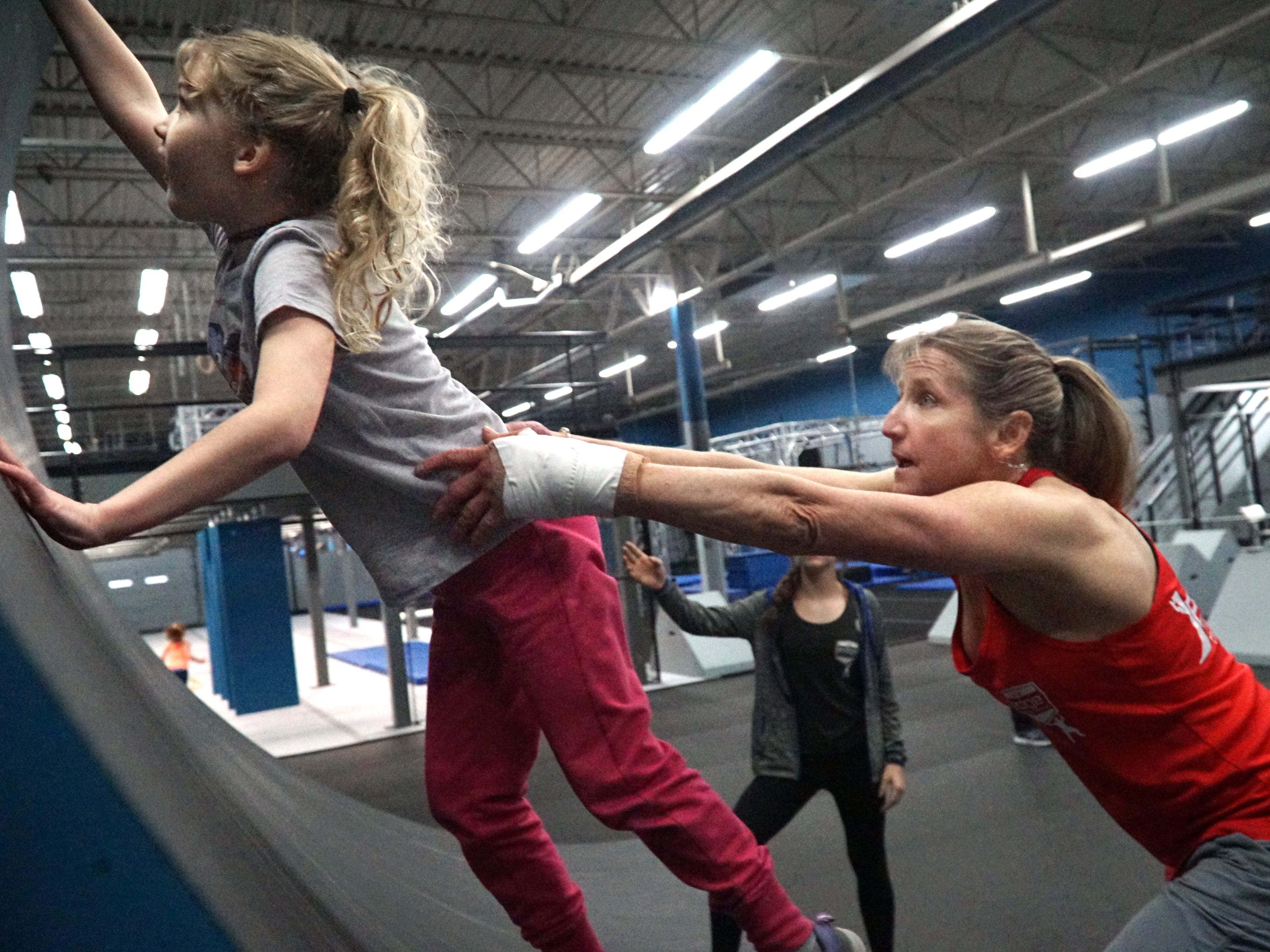 Carey Sherbrooke, right, gives a small boost to student Morgan Hudya - as the youngster tries to run up the gym's curved wall on March 12 at the Edge Training Center in Plymouth.