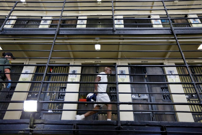 In this Aug. 16, 2016 file photo, a condemned inmate walks along the east block of death row at San Quentin State Prison in San Quentin, Calif. Gov. Gavin Newsom is expected to sign a moratorium on the death penalty in California Wednesday, March 13, 2019. (AP Photo/Eric Risberg, File)