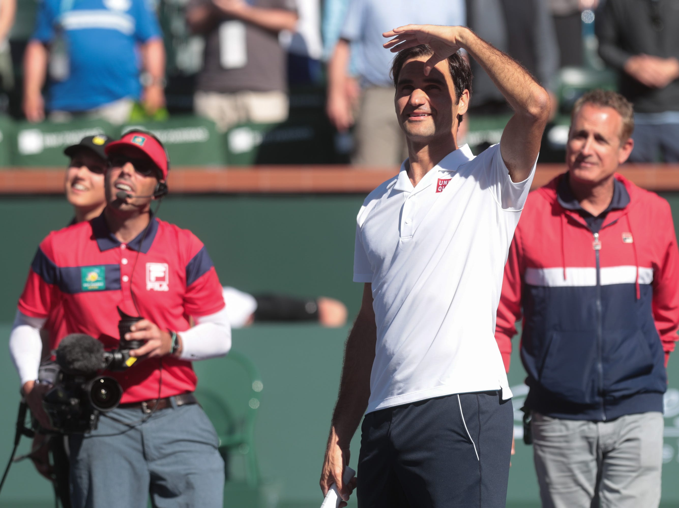 Roger Federer hits signed tennis balls into the crowd after defeating Kyle Edmund at the BNP Paribas Open in Indian Wells, Calif., March 13, 2019.