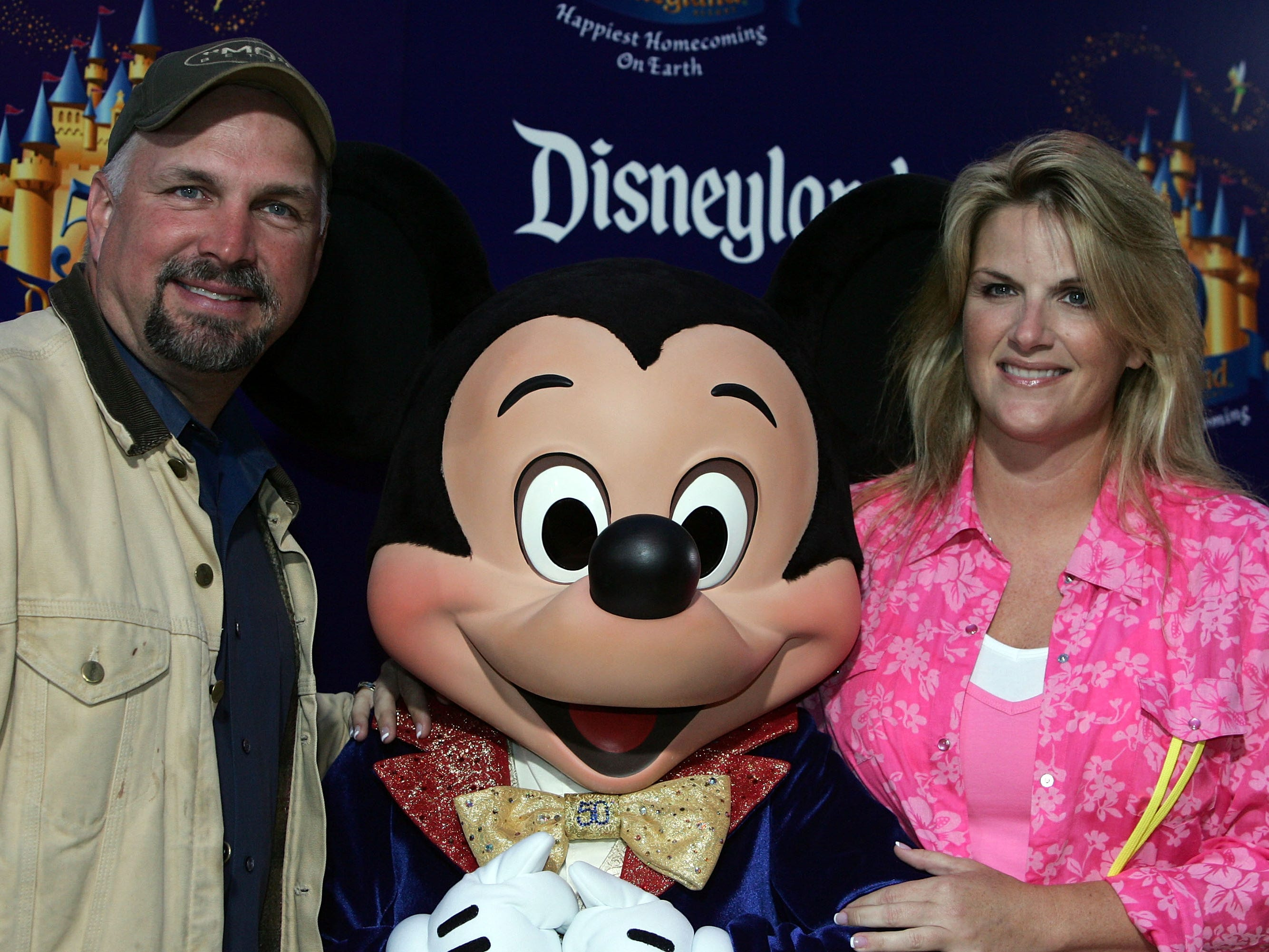 """Garth Brooks, Mickey Mouse and singer Trisha Yearwood are seen attending the """"Gold Carpet"""" arrivals on Main Street U.S.A. during the Disneyland 50th Anniversary Celebration at Disneyland Park on May 4, 2005 in Anaheim, California."""