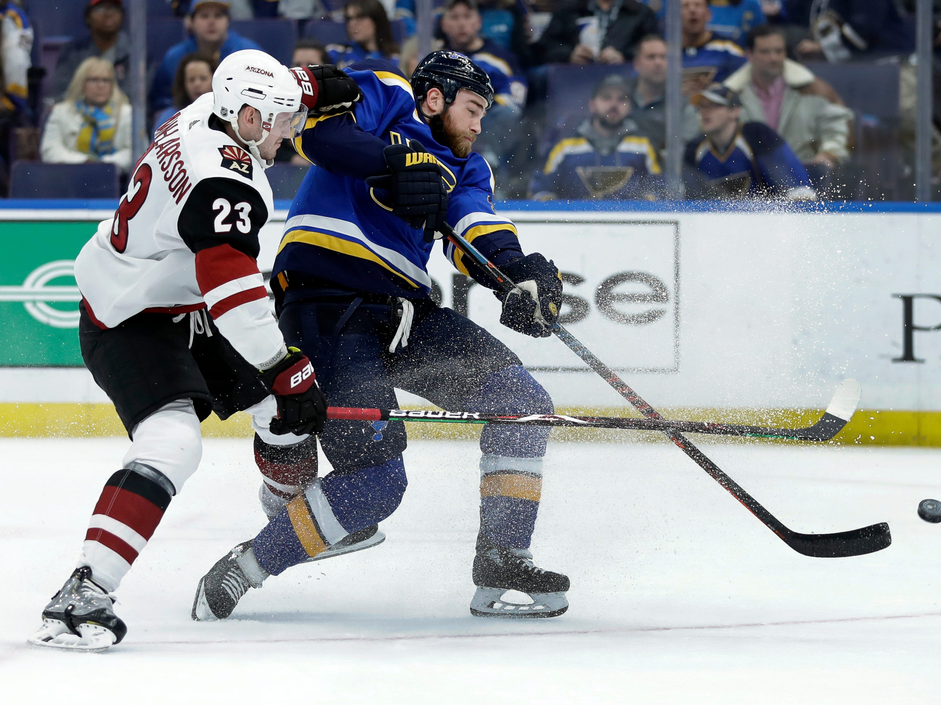 St. Louis Blues' Ryan O'Reilly, right, tries to get off a shot as Arizona Coyotes' Oliver Ekman-Larsson, of Sweden, defends during the second period of an NHL hockey game, Tuesday, March 12, 2019, in St. Louis.