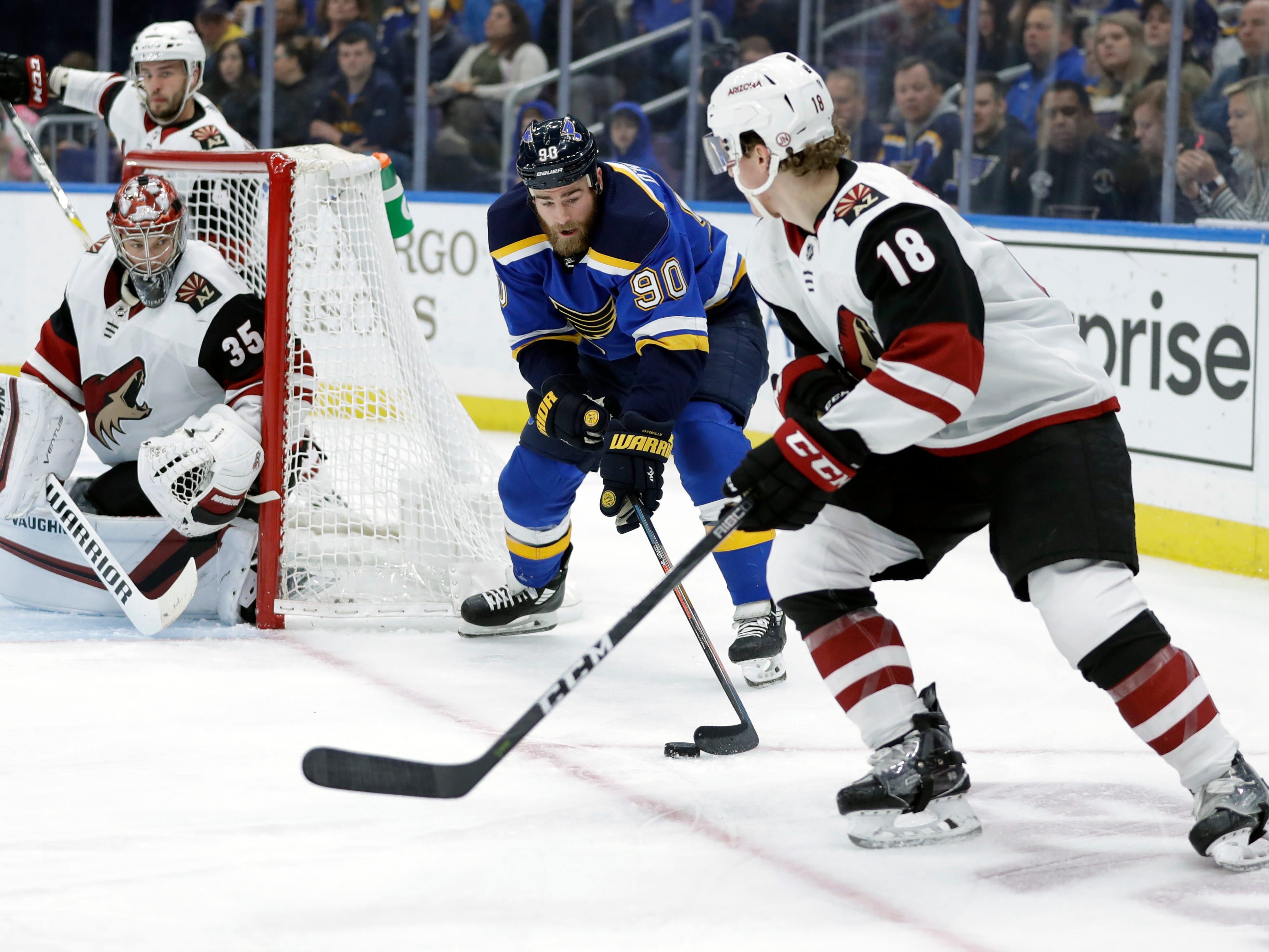 St. Louis Blues' Ryan O'Reilly (90) reaches for the puck as Arizona Coyotes goaltender Darcy Kuemper (35) and Christian Dvorak (18) defend during the second period of an NHL hockey game, Tuesday, March 12, 2019, in St. Louis.