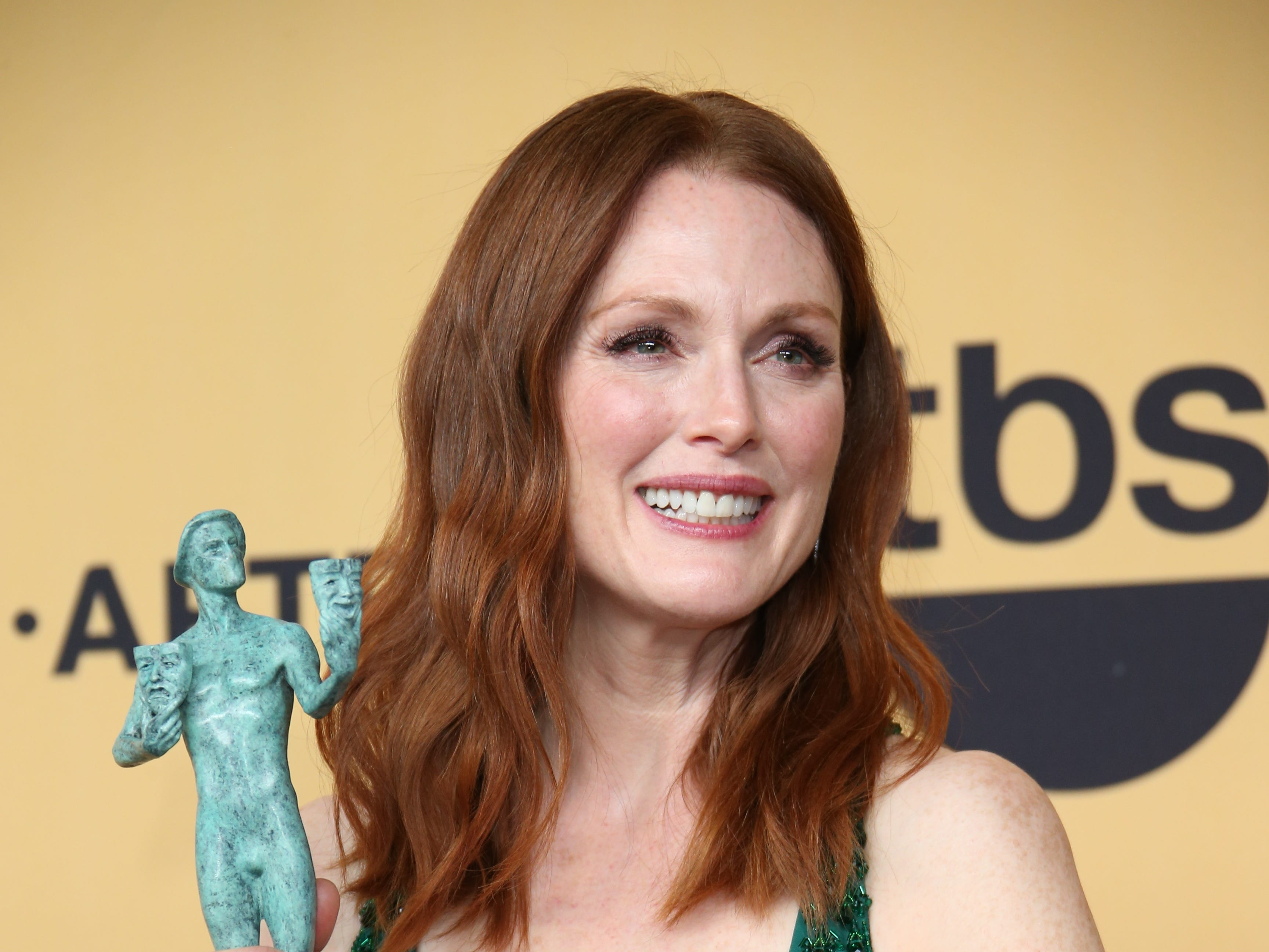 Julianne Moore poses in the photo room with her award for Female Actor in a Leading Role at the 20th Screen Actors Guild Awards held at the Shrine Auditorium in Los Angeles in 2015.