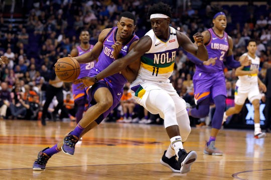 New Orleans Pelicans guard Jrue Holiday (11) pressures Phoenix Suns guard De'Anthony Melton in the second half during an NBA basketball game, Friday, March 1, 2019, in Phoenix. (AP Photo/Rick Scuteri)