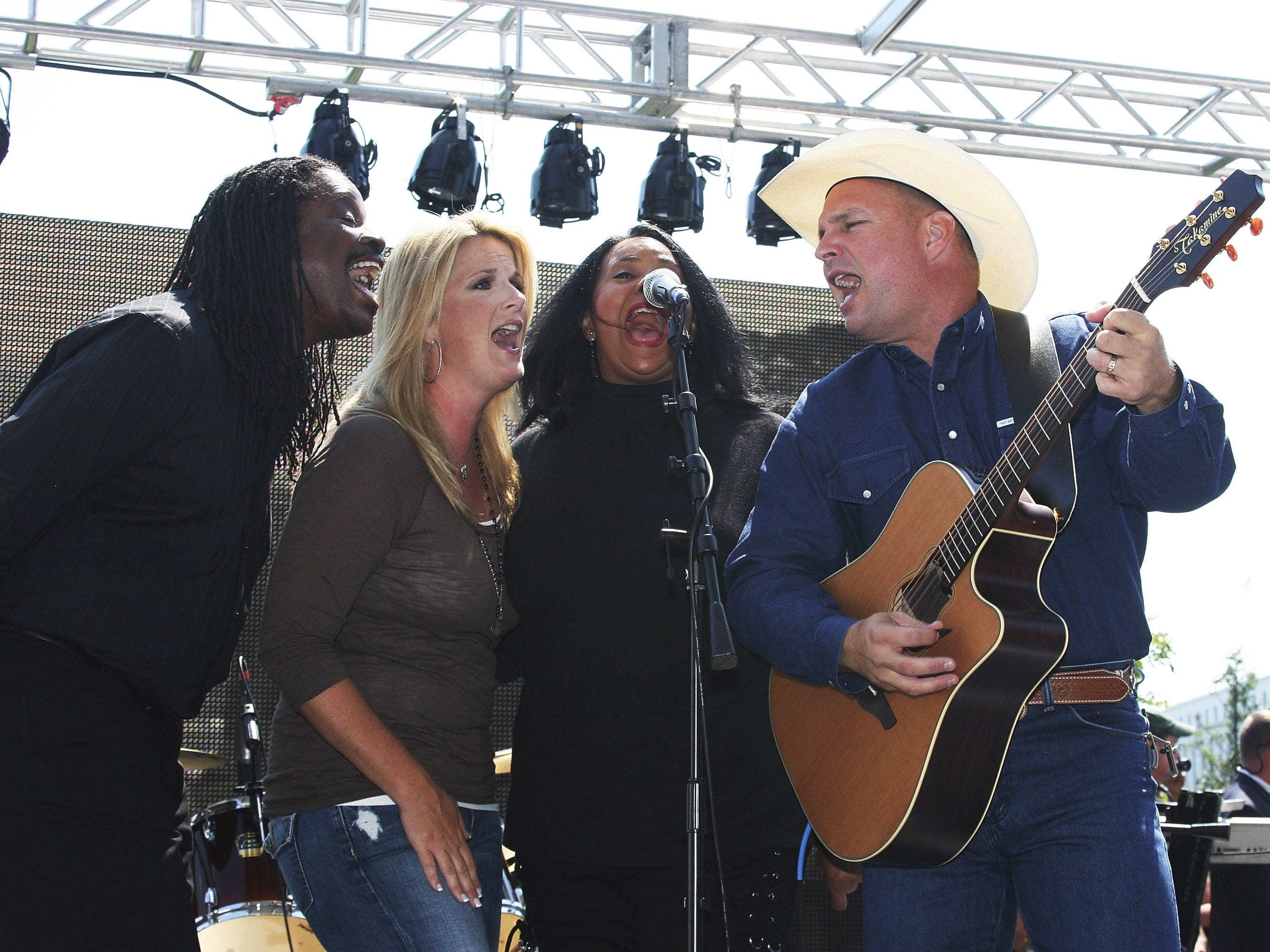 Trisha Yearwood (2nd L) and Garth Brooks (R) perform at the Live Earth show at the National Museum of the American Indian on July 7, 2007 in Washington, DC.  (Photo by Roger Kisby/Getty Images)