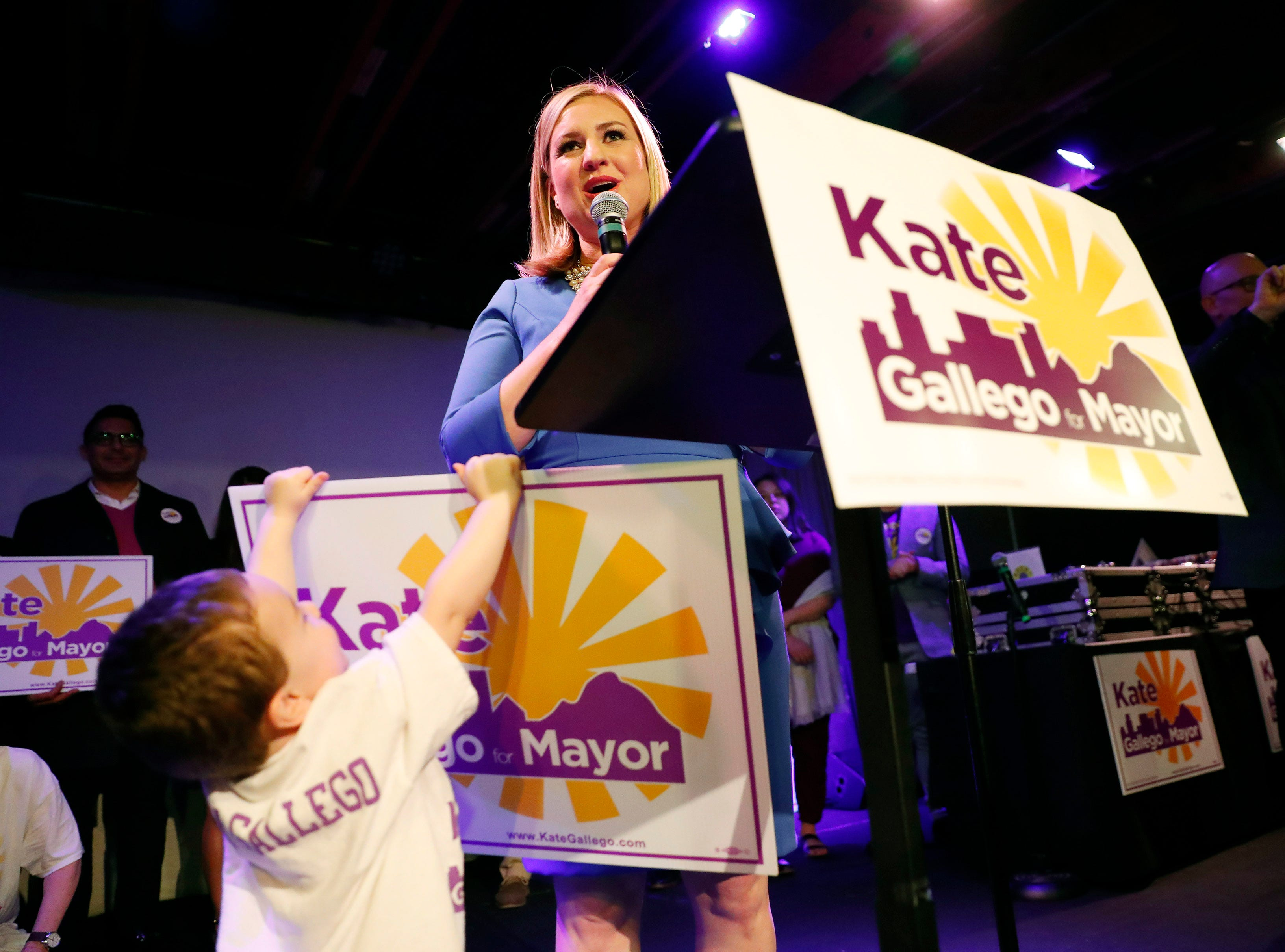 Democrat Kate Gallego talks to supporters as her son, Michael, approaches with a campaign sign during an election-night party at Crescent Ballroom in Phoenix on March 12, 2019.