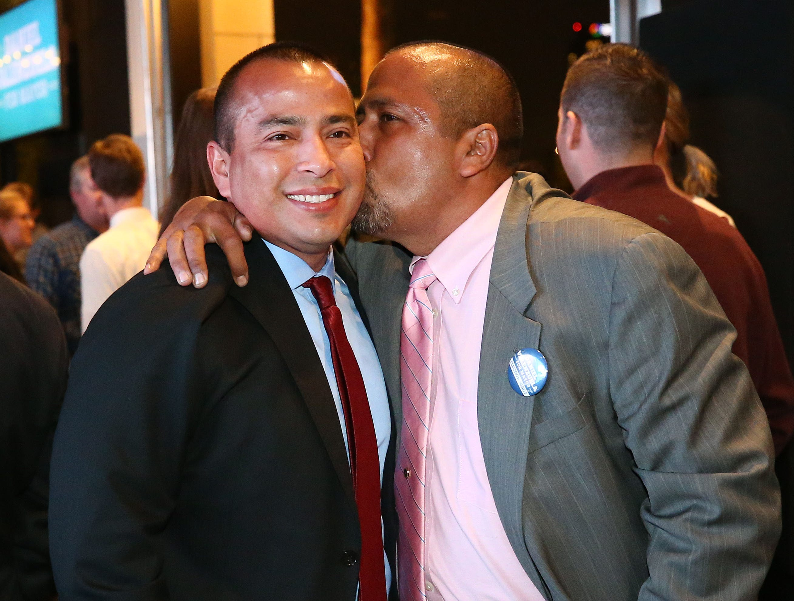 Daniel Valenzuela, candidate for Phoenix Mayor receives a kiss from his older brother Benny (right) at his election night party on Mar. 12, 2019 in Phoenix, Ariz.