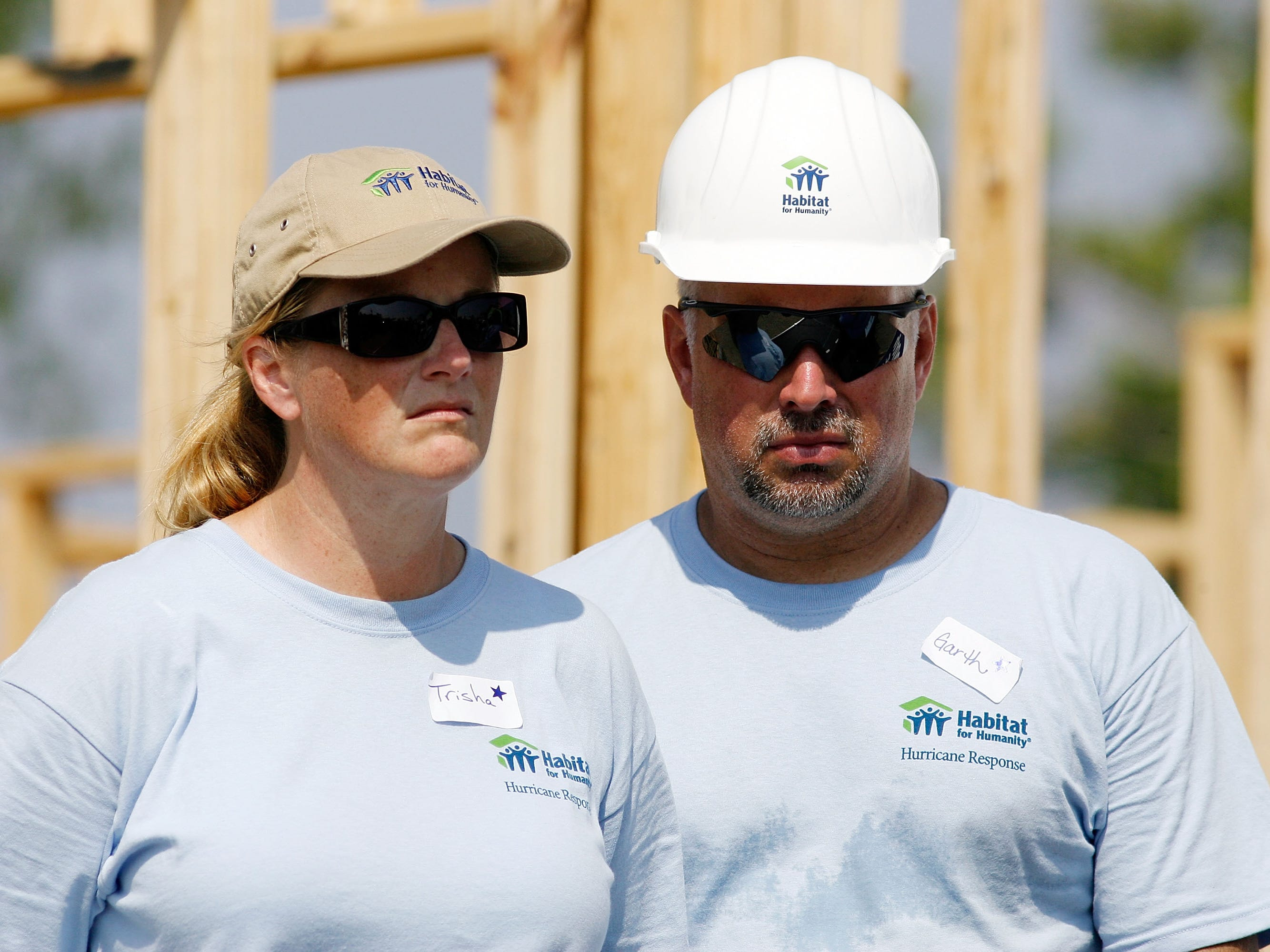Trisha Yearwood  (L) and her husband Garth Brooks listen to former U.S. President Jimmy Carter speak after raising the wall on the 1,000th and 1,001st homes to be built by Habitat for Humanity on the Gulf Coast May 21, 2007 in Violet, Louisiana.