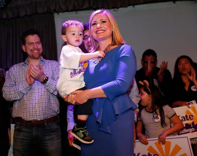 Democrat Kate Gallego holds her son, Michael, after declaring victory in the Phoenix mayoral race at an election-night party at Crescent Ballroom in Phoenix on March 12, 2019.