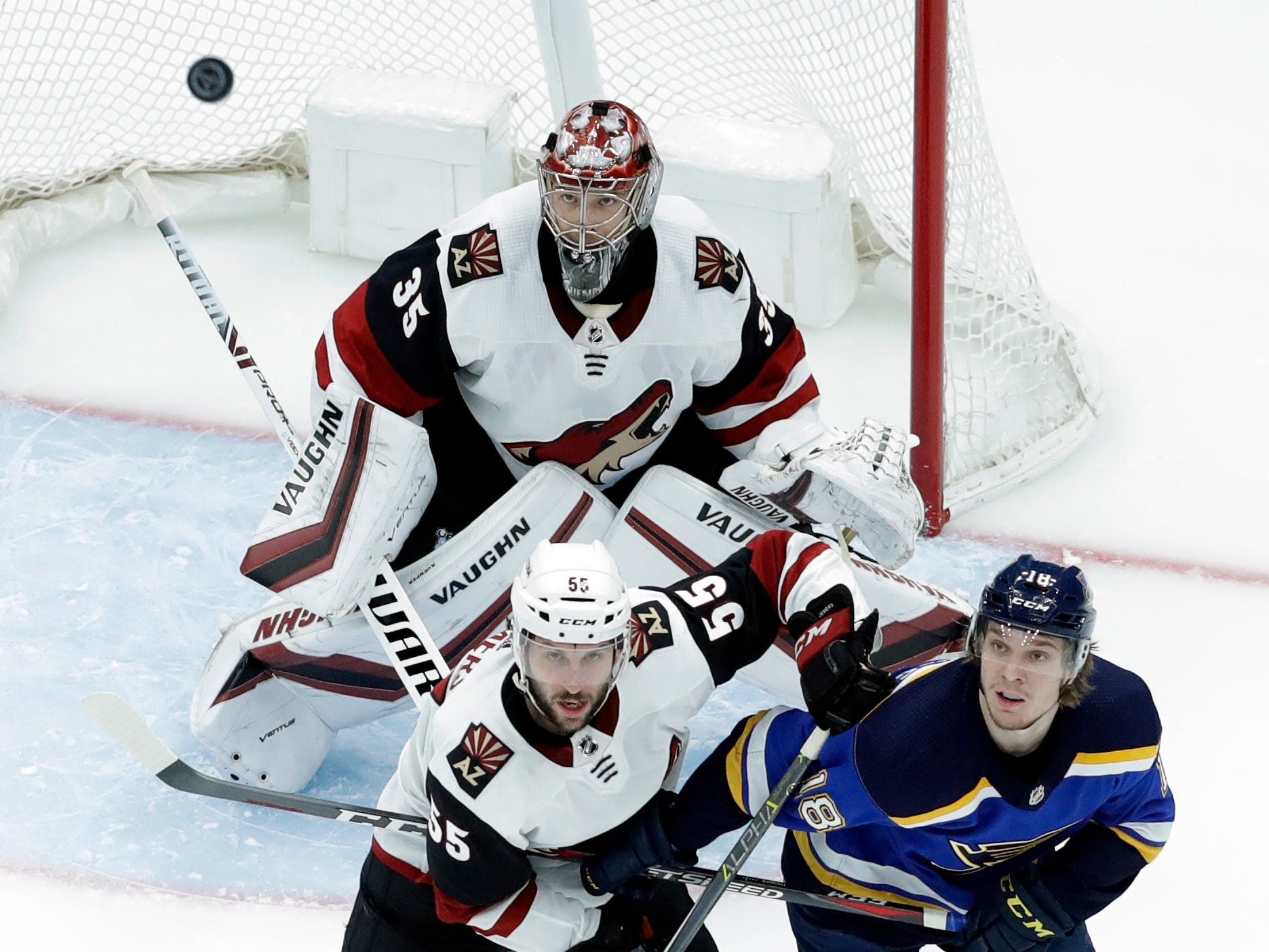 Arizona Coyotes goaltender Darcy Kuemper (35), Jason Demers (55) and St. Louis Blues' Robert Thomas (18) watch as the puck flies in the air during the first period of an NHL hockey game, Tuesday, March 12, 2019, in St. Louis.