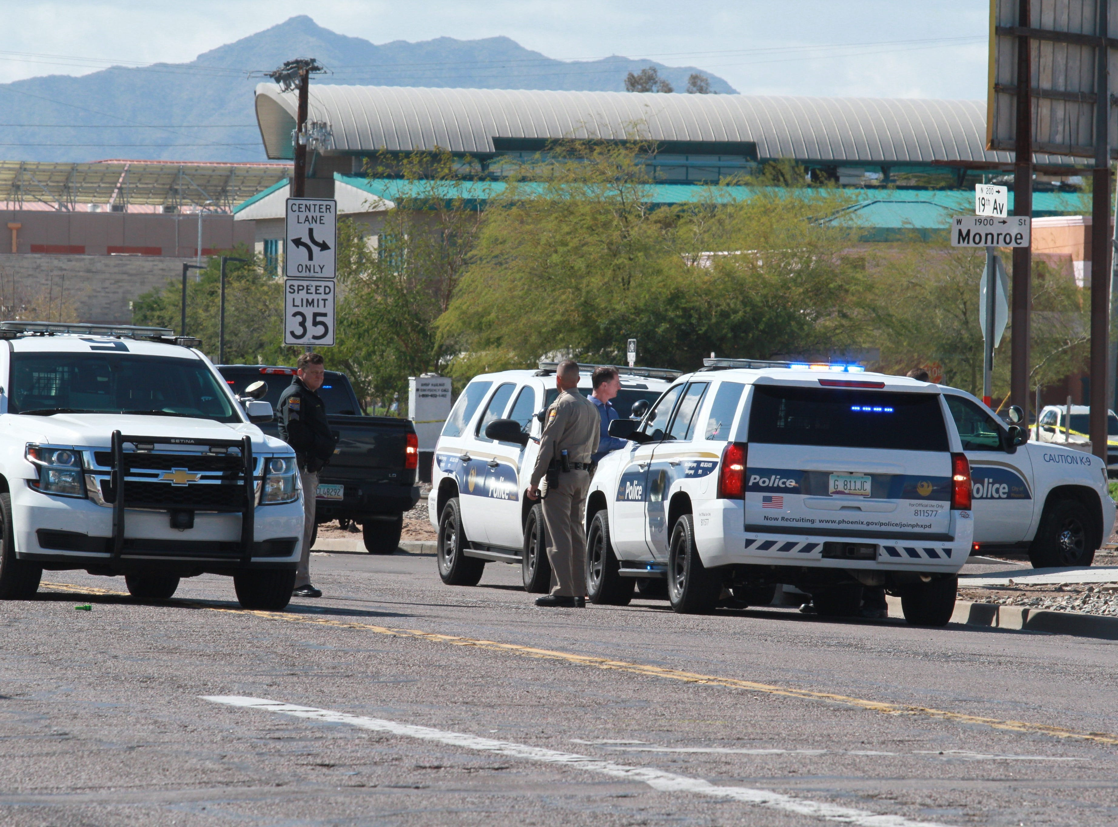 Phoenix Police Department officials at the scene of an officer-involved shooting near 19th Avenue and Monroe Street.