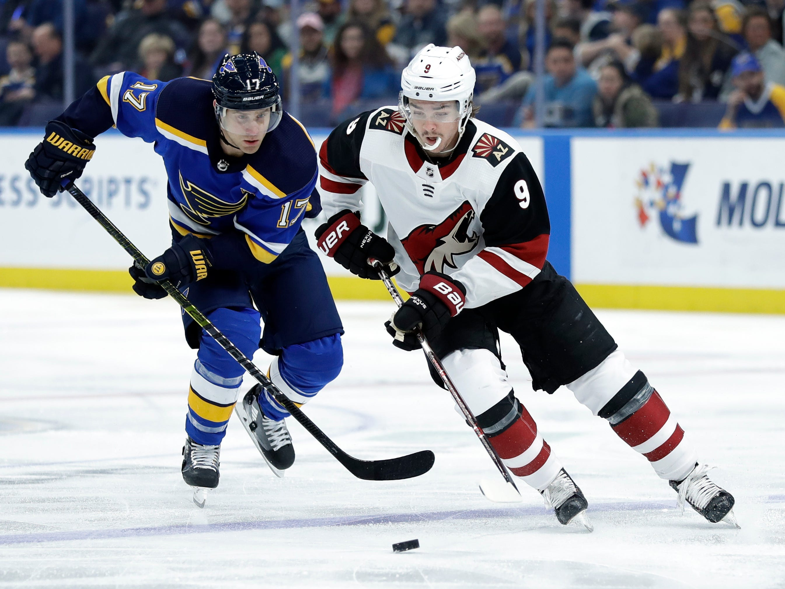 Arizona Coyotes' Clayton Keller (9) brings the puck down the ice as St. Louis Blues' Jaden Schwartz (17) gives chase during the first period of an NHL hockey game, Tuesday, March 12, 2019, in St. Louis.