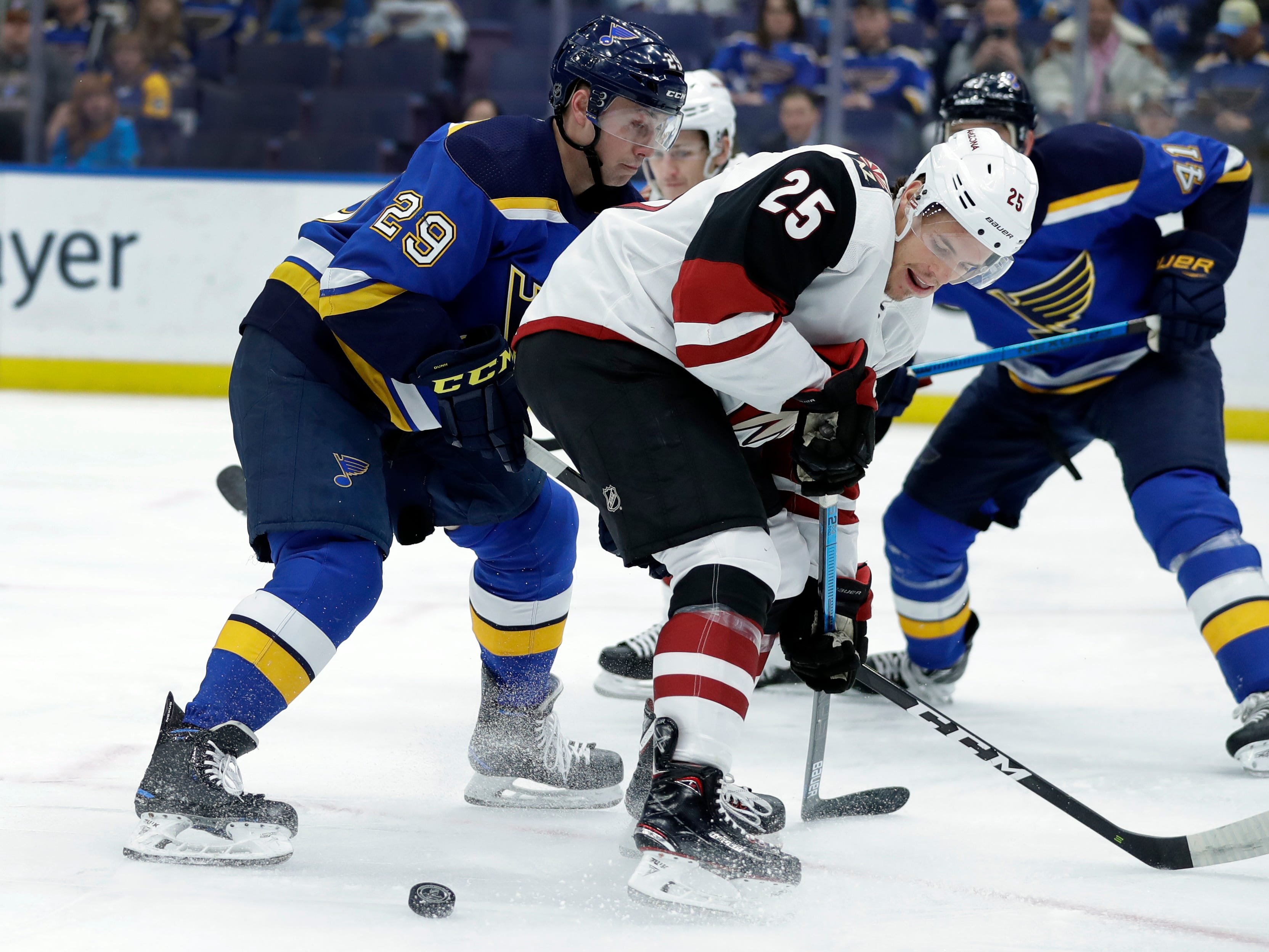 Arizona Coyotes' Nick Cousins (25) and St. Louis Blues' Vince Dunn (29) skate past the puck during the first period of an NHL hockey game, Tuesday, March 12, 2019, in St. Louis.