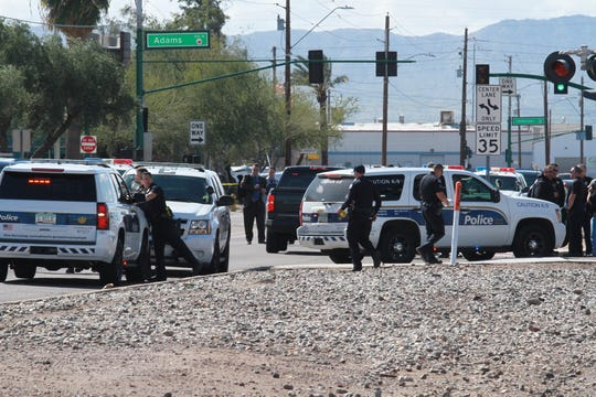 Police officers gathered near the officer-involved shooting near 19th Avenue and Monroe Street.