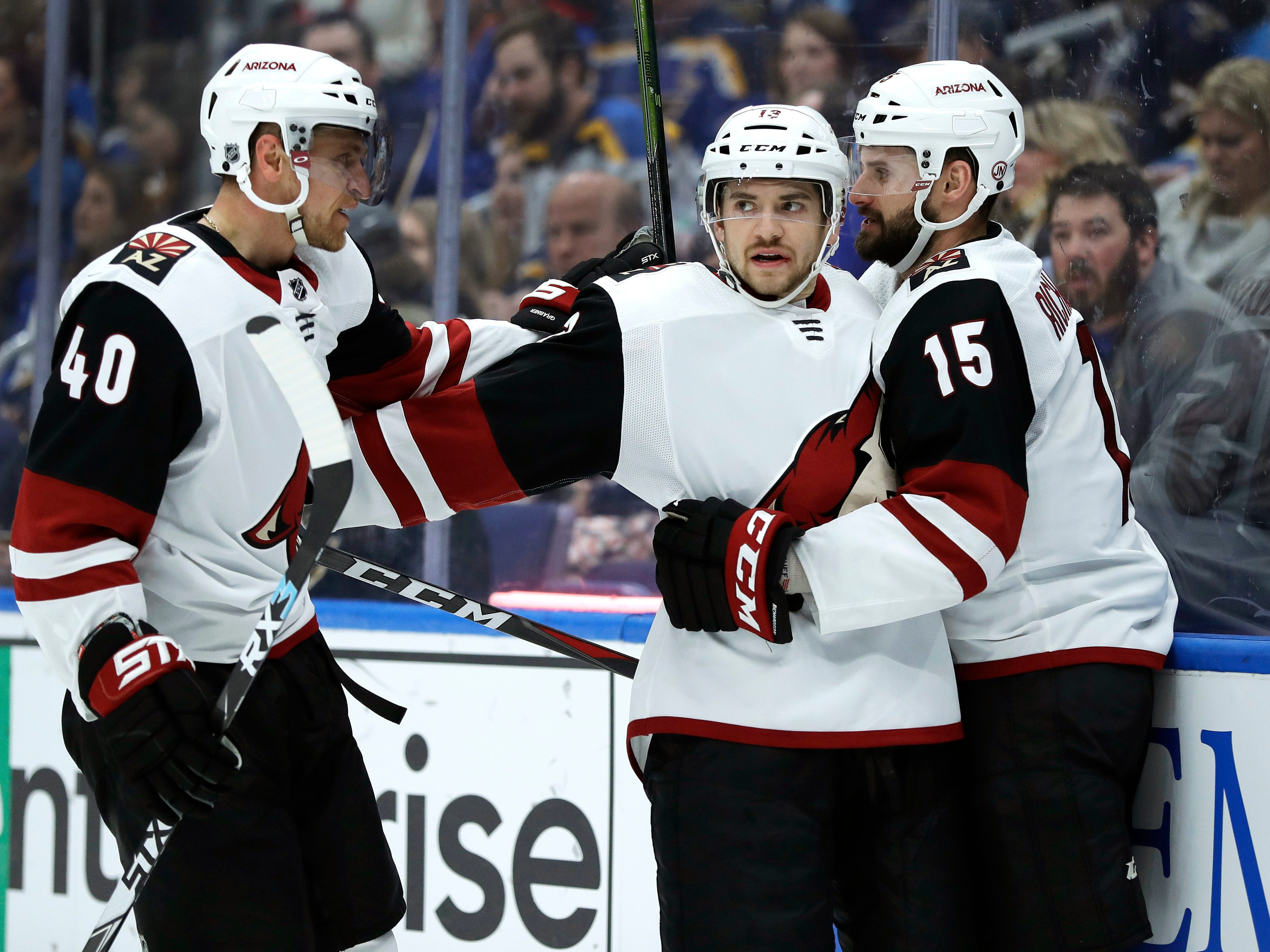 Arizona Coyotes' Vinnie Hinostroza, center, is congratulated by teammates Michael Grabner, of Austria, and Brad Richardson (15) after scoring during the third period of an NHL hockey game against the St. Louis Blues, Tuesday, March 12, 2019, in St. Louis. The Coyotes won 3-1.