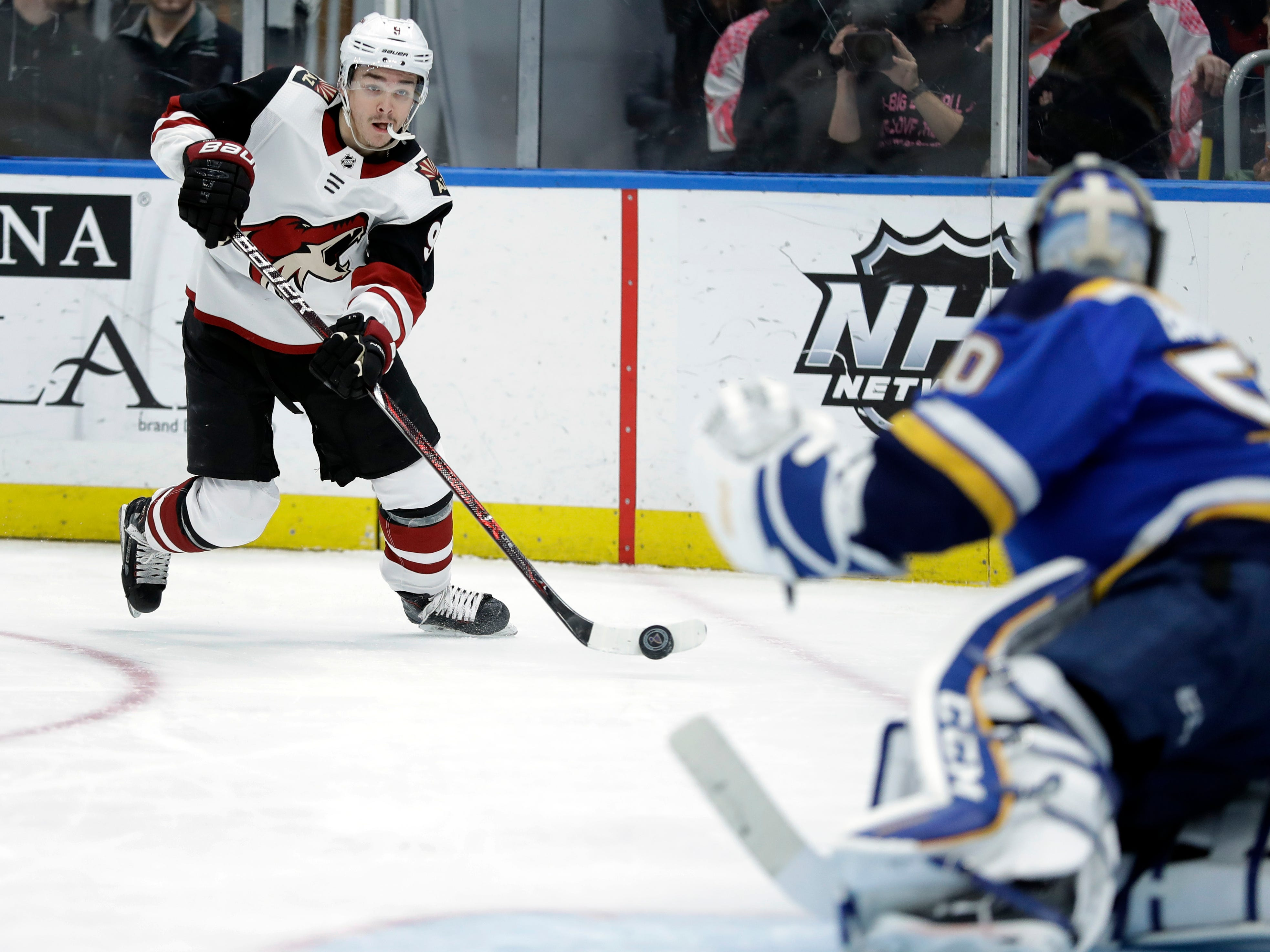 Arizona Coyotes' Clayton Keller, right, handles the puck as St. Louis Blues goaltender Jordan Binnington defends during the first period of an NHL hockey game, Tuesday, March 12, 2019, in St. Louis.
