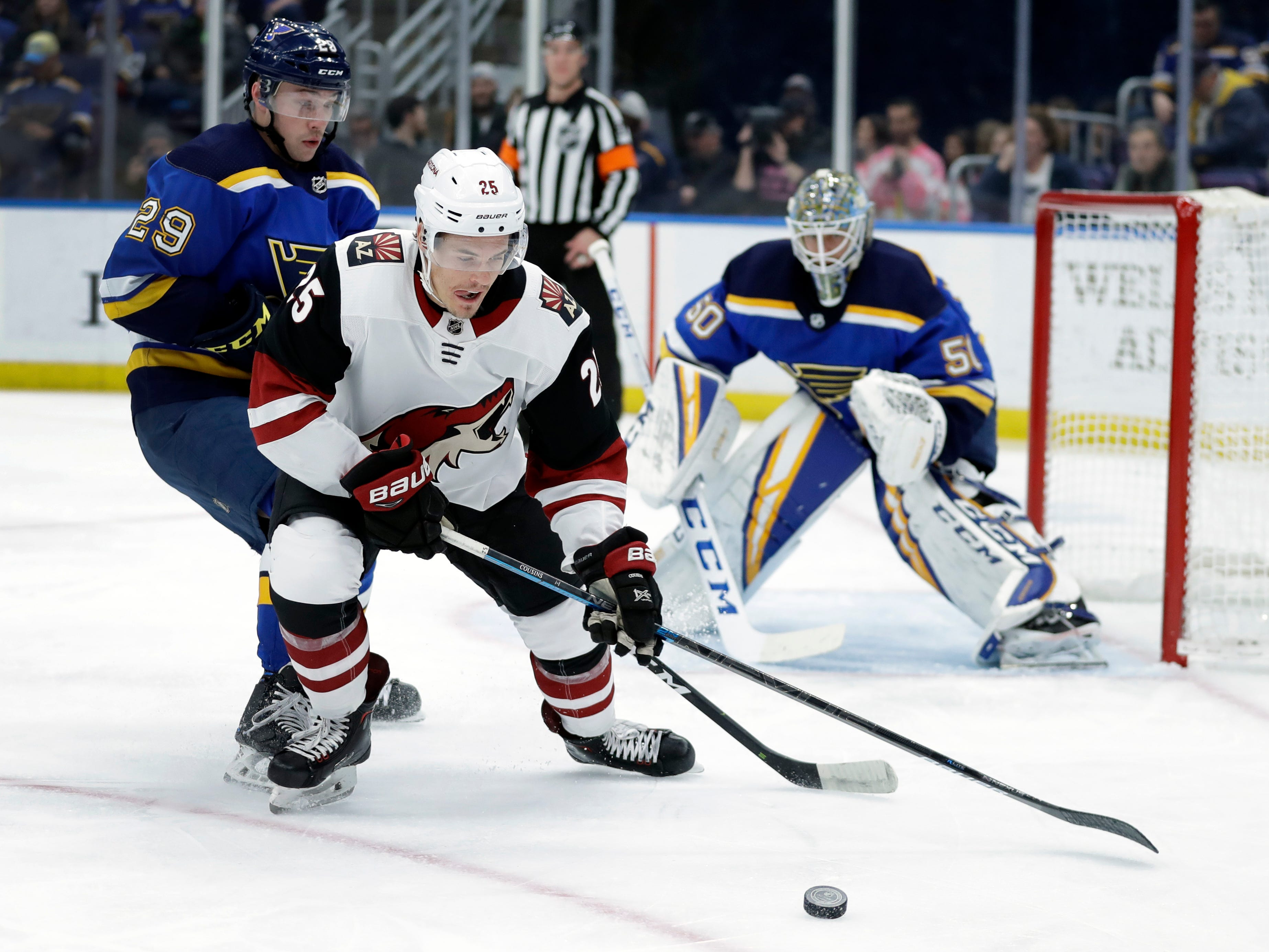 Arizona Coyotes' Nick Cousins controls the puck as St. Louis Blues' Vince Dunn (29) and goaltender Jordan Binnington (50) defend during the first period of an NHL hockey game, Tuesday, March 12, 2019, in St. Louis.