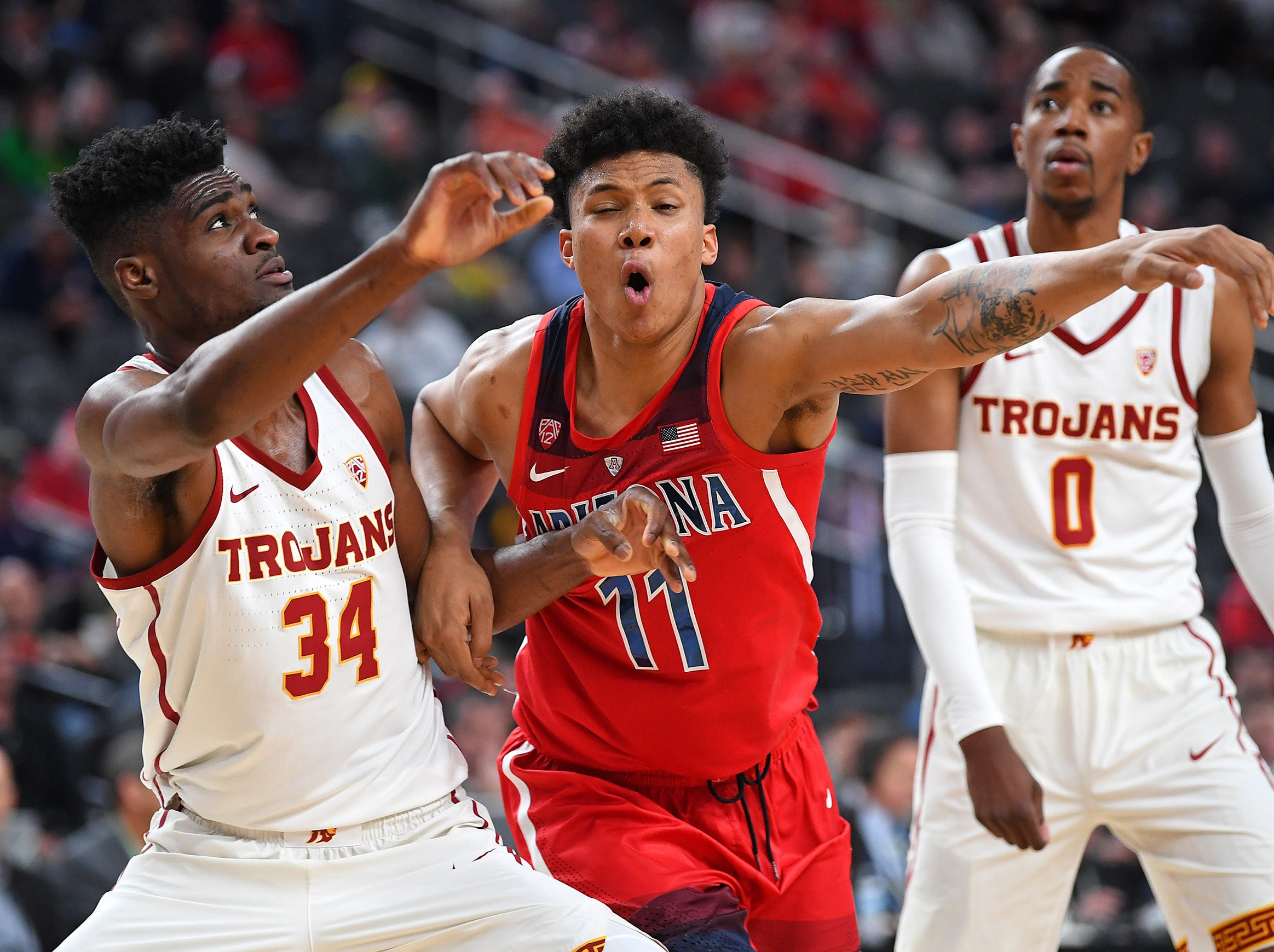 Mar 13, 2019; Las Vegas, NV, United States; USC Trojans forward Victor Uyaelunmo (34) boxes out Arizona Wildcats forward Ira Lee (11) during a first half free throw attempt in a Pac-12 conference tournament game at T-Mobile Arena. Mandatory Credit: Stephen R. Sylvanie-USA TODAY Sports