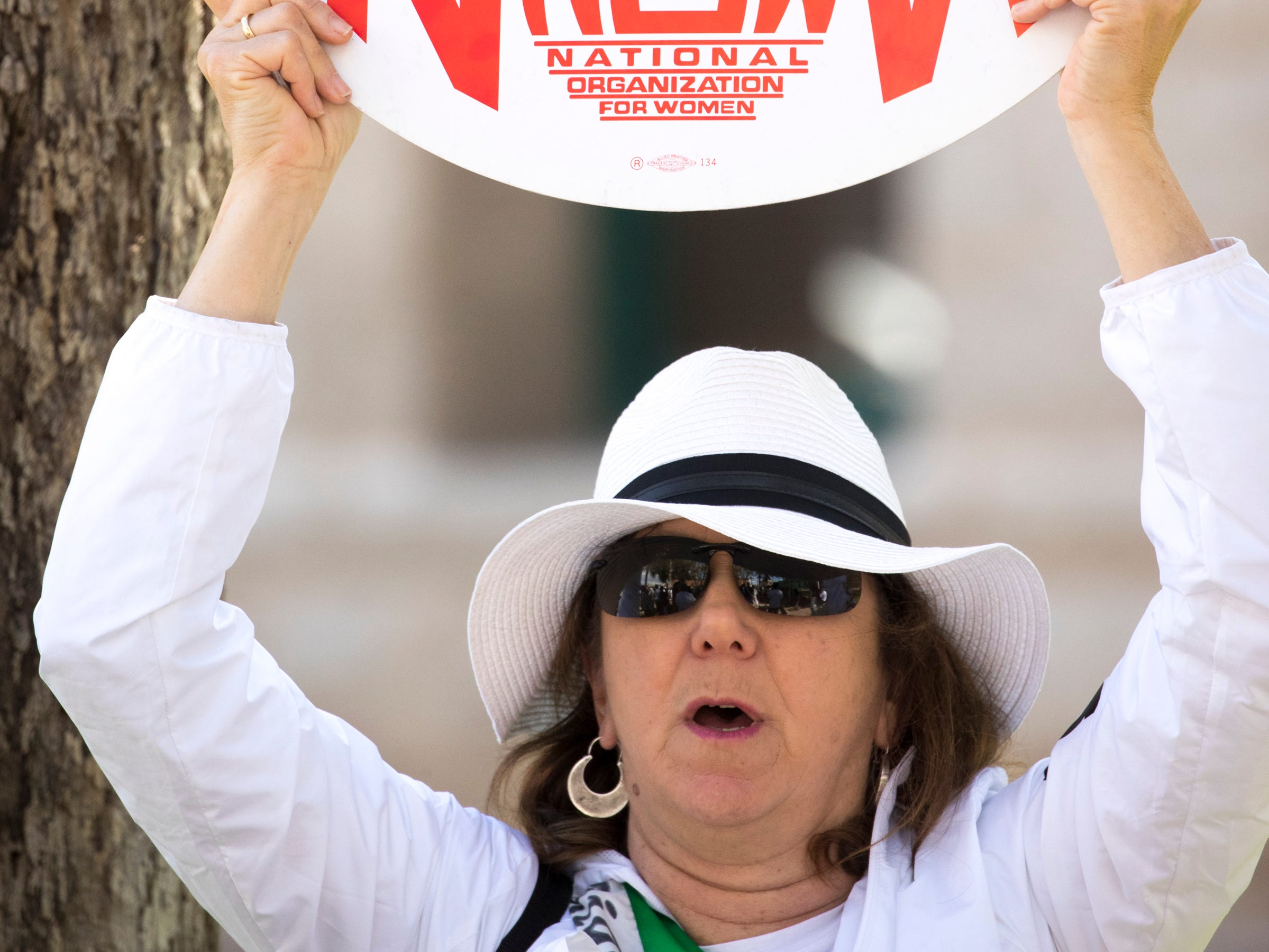 Lisa Bishop holds a sign during an ERA Rally in the Rose Garden March 13, 2019, at the Arizona state Capitol.