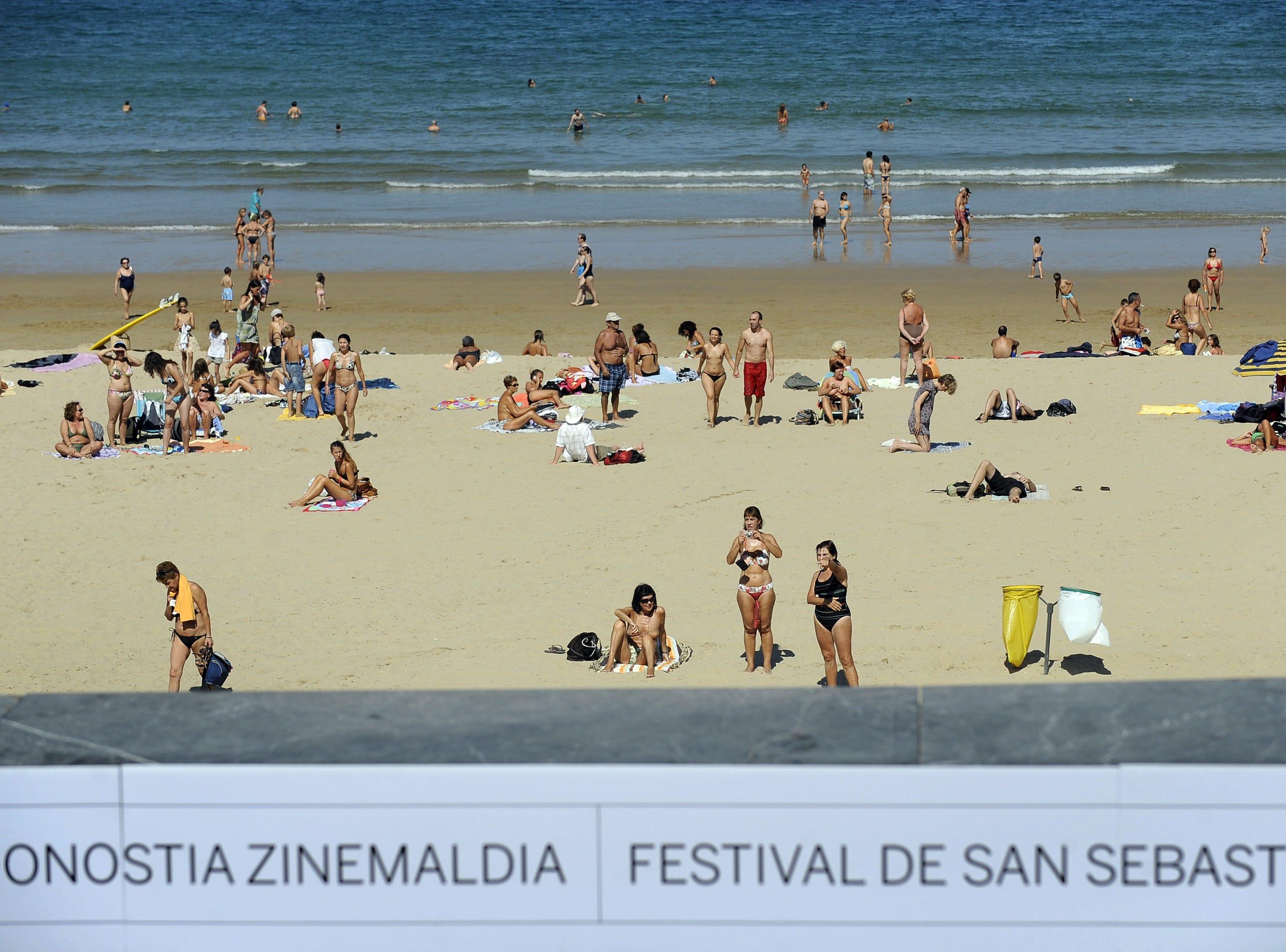 People sunbathe at Zurriola beach, next to Kursaal Palace, where the 60th San Sebastian International Film Festival is taking place, on September 22, 2012, in the northern Spanish Basque city of San Sebastian.  AFP PHOTO/ RAFA RIVAS        (Photo credit should read RAFA RIVAS/AFP/GettyImages)