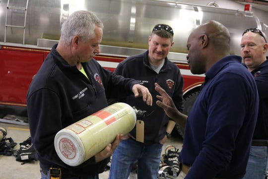 Walter Cook, right, a firefighter in Cincinnati, checks out an air tank donated by the Harris-Elmore Fire Department to soon be shipped overseas to a country in need.