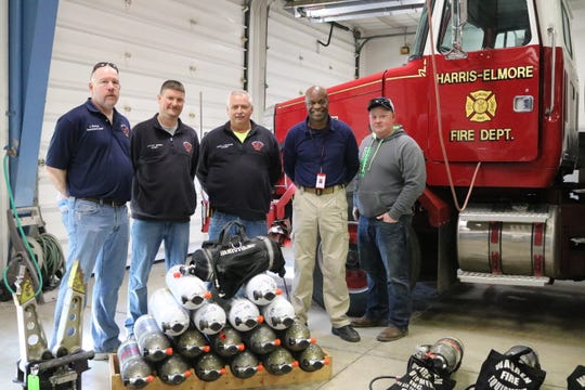 Members of the Harris-Elmore Fire Department pose with Walter Cook, a firefighter from Cincinnati, who ships donated equipment overseas to countries in need.