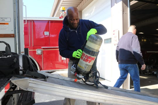 Walter Cook, a firefighter in Cincinnati, prepares several self-contained breathing apparatus donated by the Harris-Elmore Fire Department on Tuesday to soon be shipped overseas to a country in need.