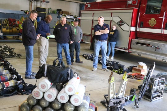 Walter Cook, second from the left, a firefighter in Cincinnati, takes note of the items donated by the Harris-Elmore Fire Department on Tuesday to soon be shipped overseas to a country in need.