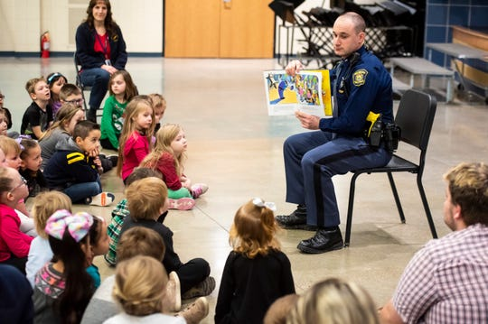 "Michigan State Police Trooper Chad Conquergood pauses while reading ""Officer Buckle and Gloria"" to show pictures from the book to a group of Capac Elementary School kindergarteners and Head Start students Wednesday, March 13, 2019 as part of the Michigan State Police Lapeer Post's Blue Plate Program at Capac Elementary. The program is usually held at lunchtime, but to celebrate Reading Month, the officer visited the school in the morning to read to students."