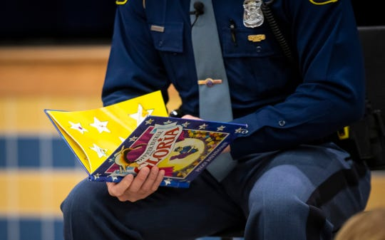 "Michigan State Police Trooper Chad Conquergood turns to the first plages of ""Officer Buckle and Gloria"" before reading the book to a group of Capac Elementary School kindergarteners and Head Start students Wednesday, March 13, 2019 as part of the Michigan State Police Lapeer Post's Blue Plate Program. The program is usually held at lunchtime, but to celebrate Reading Month, the officer visited the school in the morning to read to students."