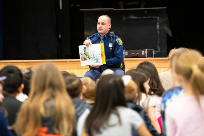 """Michigan State Police Trooper Chad Conquergood pauses while reading """"Officer Buckle and Gloria"""" to show pictures from the book to a group of Capac Elementary School kindergarteners and Head Start students Wednesday, March 13, 2019 as part of the Michigan State Police Lapeer Post's Blue Plate Program. The program is usually held at lunchtime, but to celebrate Reading Month, the officer visited the school in the morning to read to students."""
